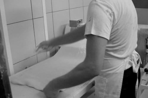 Ο Τεχνίτης μπουγάτσας την ώρα που ανοίγει το φύλλο στο χέρι. The mpougatsa expert technician at the time that produces the handmade fillo.