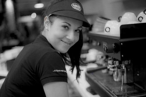 Μια γυναίκα μπαρίστα μπροστά από την μηχανή καφέ. A woman barista in front of the coffee espresso machine.